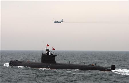 Военный самолет пролетает над китайской подводной лодкой на международном смотре флота в Циндао по случаю 60-й годовщины основания Народно-освободительной армии и военно-морского флота Китая