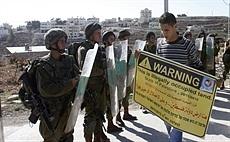 30 ноября 2012 - палестинский протестующий держит плакат перед израильскими солдатами во время демонстрации в деревне аль-Масара на Западном берегу реки Иордан, около Вифлеема.  (AP)
