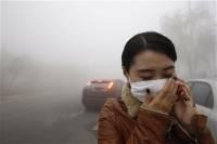 Китаянка закрывается от смога в Харбине