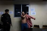 """Полицейский осматривает одного из предполагаемых лидеров картеля Синалоа в Гватемале, Wilmar Anavisca ©, также известного как """"El Chino"""", после его ареста в Верховном суде в Гватемала-Сити, 18 октября 2013 года."""