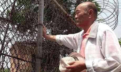 Южнокореец, Lee In-Sub, 72 лет, оставил свою семью в Северной Корее, когда бежал на юг во время Корейской выйны. Здесь он смотрит на Северную Корею через колючую проволоку у границы в 2000 году. Photograph: Hwang Kwang-mo/EPA