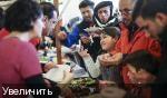REUTERS/Hannibal Hanschke. Мигранты получают еду на рождественской ярмарке в приюте для беженцев, находящемся в ведении немецкой благотворительной организации Arbeiter Samariter Bund ASB в Берлине, Германия, 12 декабря 2015 года.